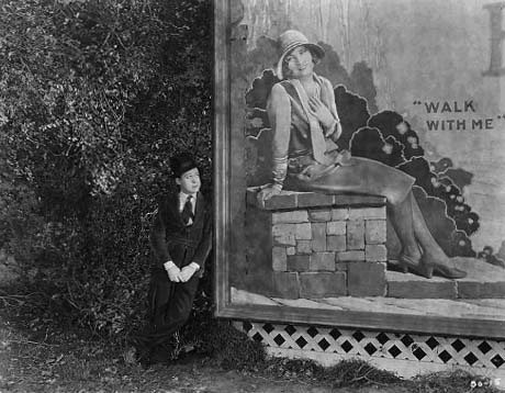 1926, 'Tramp, Tramp, Tramp.' Harry admires 'Betty' (Joan) on a billboard.