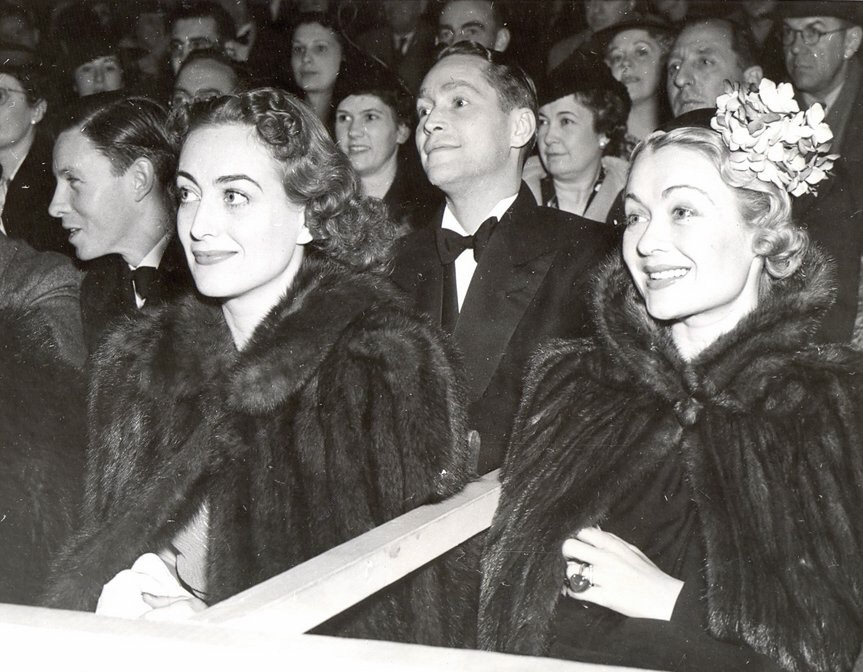 1937. At a tennis match (yes, in furs) with Franchot Tone and Constance Bennett.