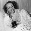 3/7/46. At home with her new Oscar for 'Mildred Pierce.'