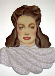 By Dale. Mixed media (satin hair, silver lame dress material). 21 x 17 inches. Year unknown.