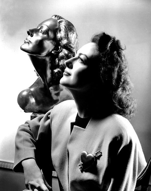 1941. With a sculpture of herself by Yucca Salamunich, presented to her on the set of 'A Woman's Face.'